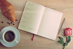 Rewolucjonistki róża i filiżanka kawy z dzienniczkiem z dniem i croissant Zdjęcia Royalty Free