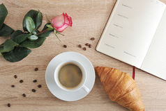 Rewolucjonistki róża i filiżanka kawy z dzienniczkiem z dniem i croissant Fotografia Stock