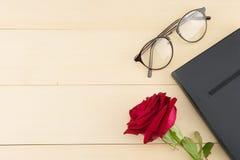 Rewolucjonistki róża, szkła i czarny notatnik, fotografia royalty free