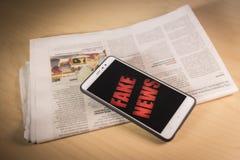 Rewolucjonistki wiadomości sfałszowani słowa na ekranie nad gazetą Sfałszowana wiadomość, bajerowania pojęcie fotografia royalty free