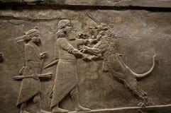 Rey asirio que mata a un león Imágenes de archivo libres de regalías