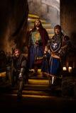 Rey medieval con sus caballeros en interior antiguo del castillo imagen de archivo