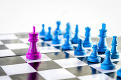 Rey púrpura que amenaza al equipo azul en un tablero de ajedrez imagen de archivo libre de regalías