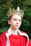 Rey temporario de la corona del muchacho que lleva adolescente Fotos de archivo