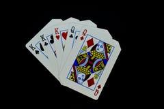 Reyes de la casa llena sobre tarjetas de las reinas en juego de póker contra fondo negro fotos de archivo