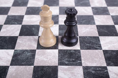 Reyes de madera blancos y negros en el tablero de ajedrez Foto de archivo