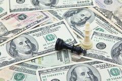 Reyes del ajedrez en la pila de billetes de banco del dólar de EE. UU. Fotos de archivo libres de regalías