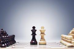 Reyes del juego de ajedrez dos en el centro del tablero que otros pedazos se alinearon fotografía de archivo