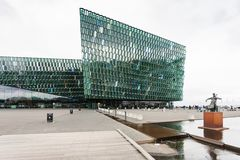 Harpa and cellist statue in Reykjavik city. REYKJAVIC, ICELAND - SEPTEMBER 5, 2017: view of Harpa and cellist statue in Reykjavik. Harpa was designed by the firm stock image