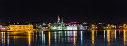 Reykjavik central by night. Reykjavik, Iceland, on a cold but still winter night with the city lights reflecting in a frozen pond royalty free stock images