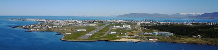 Reykjavik airport and the Reykjavik city on it`s peninsula which is surrounded by the ocean.