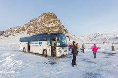 Reykjavik Excursions. REYKJAVIK, ICELAND - January 18, 2015: Tour bus having a break in front of Eyjafjallajokull Mountain. Reykjavik Excursions is a leading royalty free stock photos