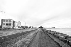 City roads along sea on cloudy sky. Promenade at seaside. Freedom, perspective and future. Travel and wanderlust on. Reykjavik, Iceland - October 12, 2017: city royalty free stock images