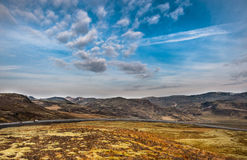 REYKJAVIK, ICELAND - OCTOBER 15, 2014: Iceland Landscape Nature with Moss on Lava Ground. Road and Blue Sky Stock Images