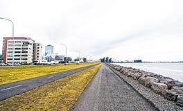 Reykjavik, IJsland - Oktober 12, 2017: stadswegen langs overzees op bewolkte hemel Promenade bij kust Vrijheid, perspectief stock foto's