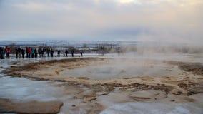 Reykjavik Island - Januari 2016: Turister som väntar på utbrottet av den Strokkur geyseren i Island Arkivbild