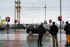 REYKJAVIK ISLAND - 12 MARS - oidentifierad turist som väntar till att korsa vägen, med röda trafikljus och zebramarkeringen tecke Arkivfoton