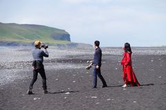 Unidentified tourists taking photograph at Reynisdrangar beach in Iceland. Stock Images
