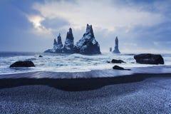 Reynisdrangar es pilas volcánicas del mar del basalto situadas debajo de los acantilados de la montaña Reynisfjall cerca del pueb fotos de archivo