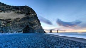 Reynisdrangar on Reynisfjara Beach. Wide view of Reynisdrangar rock formations on Reynisfjara Beach at sunrise, Halsanefhellir, Iceland Stock Photos
