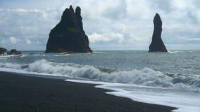 Reynisdrangar rock formations at Reynisfjara Beach. Coast of the Atlantic ocean, southern Iceland. Famous Reynisdrangar rock formations at black Reynisfjara stock video