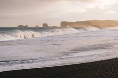 Reynisfjara beach and Cape Dyrholaey in Iceland. Reynisfjara beach with black volcanic sand. View of Cape Dyrholaey. A storm on the ocean with big waves. Tourist stock photos