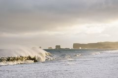 Reynisfjara Beach, Iceland. View of Cape Dyrholaey from Reynisfjara Beach, Iceland. Big waves on the ocean. Stormy weather with strong wind. Beautiful evening stock photo