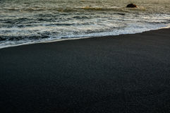 Reynisfjara black sand beach and ocean waves near  Vik town. Iceland at sunset on sunny summer day Stock Image