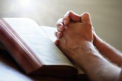 Rezando as mãos em uma Bíblia Sagrada Fotografia de Stock Royalty Free