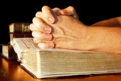 Rezando as mãos na luz com as Bíblias Sagradas Foto de Stock