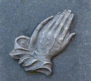 Rezando as mãos na sepultura Foto de Stock