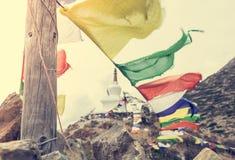 Rezando bandeiras com o stupa no fundo Fotografia de Stock