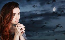Rezando a mulher contra o céu nebuloso com lua foto de stock royalty free