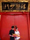 Rezar indo dos pares chineses novos no templo Imagem de Stock