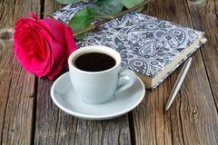 Rezerwuje z pięknymi różami up i filiżanką kawy na drewnianym stołu zakończeniu Zdjęcie Royalty Free