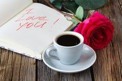 Rezerwuje z pięknymi różami up i filiżanką kawy na drewnianym stołu zakończeniu Fotografia Royalty Free