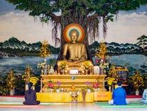 Rezo dentro de un templo budista en Vietnam, adoración de la estatua de Buda en un templo antiguo en ciudad del turista de Hoi An Imagen de archivo libre de regalías