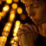Rezo que ruega en iglesia católica cerca de velas Imagen de archivo