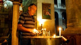 Rezos que encienden velas en la iglesia de Santo Sepulcro Imagen de archivo