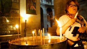 Rezos que encienden velas en la iglesia de Santo Sepulcro Fotografía de archivo libre de regalías
