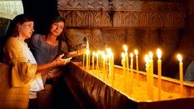 Rezos que encienden velas en la iglesia de Santo Sepulcro Imagenes de archivo