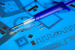 RFID implantation syringe and RFID tags. RFID implantation syringe and chips on RFID tags, blue background Stock Photo