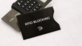 RFID-skyddsmuff för säker kreditkort från radion som stjäler pengar, SOLBRÄND generator med kortet på mittjordning Royaltyfria Bilder
