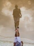 Réflexion d'une femme supérieure sur le sable humide sur une plage Photos libres de droits
