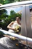 Réflexion de mariée heureuse dans l'hublot de limousine de mariage Photographie stock libre de droits