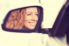 Réflexion heureuse de conducteur de femme dans le miroir de vue de côté de voiture Photos stock