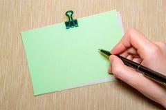 rgeen le papier avec la main de trombone et de femme tenant un stylo environ pour écrire Objets d'isolement sur le jaune Images stock