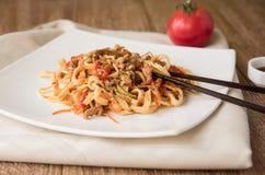Ärgern Sie Udonnudeln mit Schweinefleisch, Gemüse und Samen des indischen Sesams auf einer weißen Platte, Holztisch, Ñ- hinese E Lizenzfreie Stockfotos