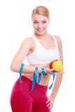 Régime La fille convenable de femme de forme physique avec la bande de mesure et la pomme portent des fruits Photographie stock