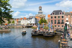 Rhine canal with cafe and church tower, Leiden, Netherlands Stock Images